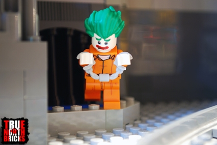 Joker running into the train tunnel with the sewer grate closed behind him.